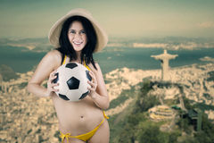 Cheerful woman holding ball in Brazil 2. Portrait of sexy woman wearing bikini holding a soccer ball Stock Image