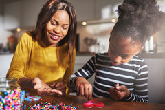 Cheerful woman holding beads for child at table Royalty Free Stock Photos