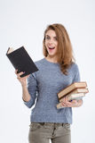 Cheerful woman holding books. Portrait of a cheerful woman holding books and looking at camera isolated on a white background Royalty Free Stock Photos