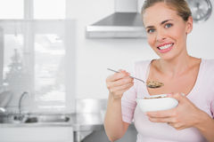 Cheerful woman holding bowl of cereal Stock Image