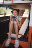 Cheerful woman holding camera while sitting in motor home Stock Image