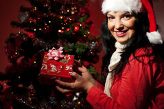 Cheerful woman holding Christmas gift Royalty Free Stock Images