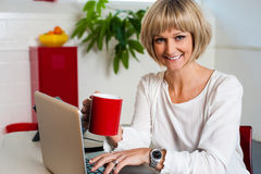 Cheerful woman holding coffee mug and working Royalty Free Stock Images