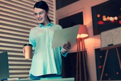 Cheerful woman holding coffee and printout with bar graph. Professional analyst. Charming dark-haired woman standing near her work desk, holding a cup of coffee stock photography