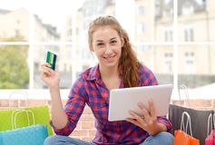 Cheerful woman holding credit cards after shopping Royalty Free Stock Photo