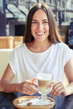 Cheerful woman holding cup of cappuccino Stock Photography