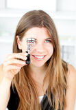 Cheerful woman holding an eyelash curler Stock Photo