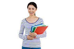 Cheerful woman holding files. Portrait of cheerful woman holding files against white background Royalty Free Stock Image