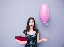 Cheerful woman holding gift box and balloon Stock Photography
