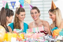 Cheerful woman holding a gift box during a surprise birthday party. Cheerful women holding a gift box while looking up overwhelmed by the appreciation of her stock photo