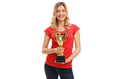 Cheerful woman holding a golden trophy. And looking at the camera isolated on white background royalty free stock image