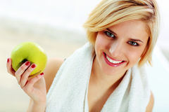 Cheerful woman holding green apple Royalty Free Stock Images