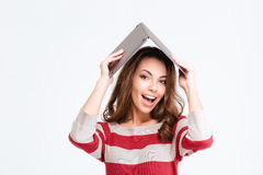 Cheerful woman holding laptop computer over head. Portrait of a cheerful woman holding laptop computer over head isolated on a white background Stock Images