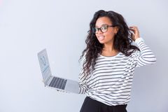Cheerful woman holding laptop. Cheerful user. Glad delighted woman using laptop and expressing gladness while standing isolated on white background royalty free stock image