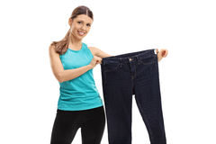 Cheerful woman holding a pair of oversized jeans Stock Photography