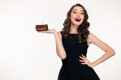 Cheerful woman holding piece of chocolate birthday cake with candle. Cheerful charming retro styled young woman holding piece of chocolate birthday cake with Royalty Free Stock Photo