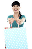 Cheerful woman holding polka dot shopping bags Royalty Free Stock Photography
