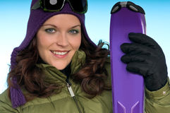 Cheerful woman holding purple skis Royalty Free Stock Photography