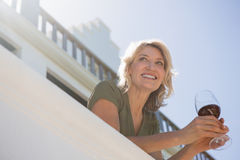 Cheerful woman holding red wine glass in balcony at restaurant. Low angle view of cheerful woman holding red wine glass in balcony at restaurant Stock Photos