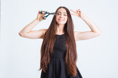 Cheerful woman holding scissors against eye and showing peace sign Royalty Free Stock Images