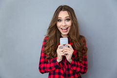 Cheerful woman holding smartphone Royalty Free Stock Photography