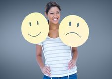 Cheerful woman holding smiley and sad face Stock Photo