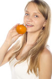 Cheerful woman holding a tangerine Royalty Free Stock Images