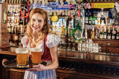 Cheerful woman holding tray with beer glasses Royalty Free Stock Image