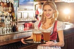 Cheerful woman holding tray with beer glasses Stock Image