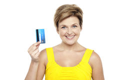 Cheerful woman holding up her cash card Stock Photos