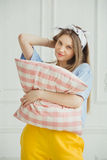 Cheerful woman holds pillow in hands. Girl without make up Royalty Free Stock Image