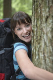 Cheerful Woman Hugging Tree In Forest Stock Photo