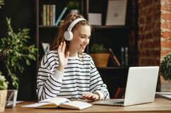 Free Cheerful Woman In Headphones Greeting Friend While Talking On Laptop At Home Stock Image - 177460441