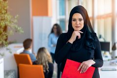 Free Cheerful Woman In The Office, Holding Folder With Documents And Giving A Bright Smile. Muslim Women Employment. Royalty Free Stock Images - 163944739
