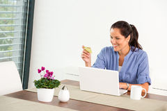 Cheerful woman internet home banking card laptop Royalty Free Stock Images