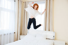 Cheerful woman jumping on the bed Stock Images