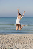 Cheerful woman jumping laughing at beach portrait. Girl young cheerful woman jumping in the air on the beach in the sand in the morning on the sea in summer Royalty Free Stock Photos