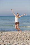 Cheerful woman jumping laughing at beach portrait. Girl young cheerful woman jumping in the air on the beach in the sand in the morning on the sea in summer Royalty Free Stock Images