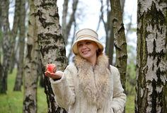 The cheerful woman keeps decorative apple on a palm in a hat Stock Photo