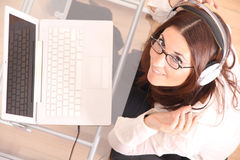Cheerful Woman with a Laptop and Headphones Royalty Free Stock Images