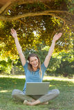 Cheerful woman with laptop raising hands at park Stock Images