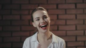 Cheerful woman laughing and posing to camera in studio with brick wall stock video