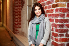 Cheerful woman leaning on the brick wall Royalty Free Stock Photo