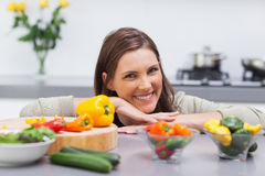 Cheerful woman leaning on the counter of her kitchen Royalty Free Stock Photos