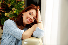 Cheerful woman leaning on the sofa Stock Image