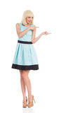 Cheerful woman in light blue color dress pointing Stock Images