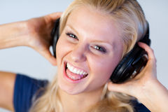 Cheerful woman listening music with headphones Royalty Free Stock Images
