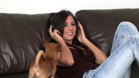 Cheerful woman listening music and playing with her dog Royalty Free Stock Image