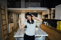Cheerful woman listening to music with large headphones and singing.Music therapy,mood beneficial practice.Mental health. Improvement,relaxation and stress stock photo