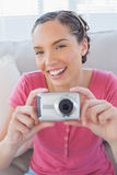 Cheerful woman in living room taking pictures Stock Image